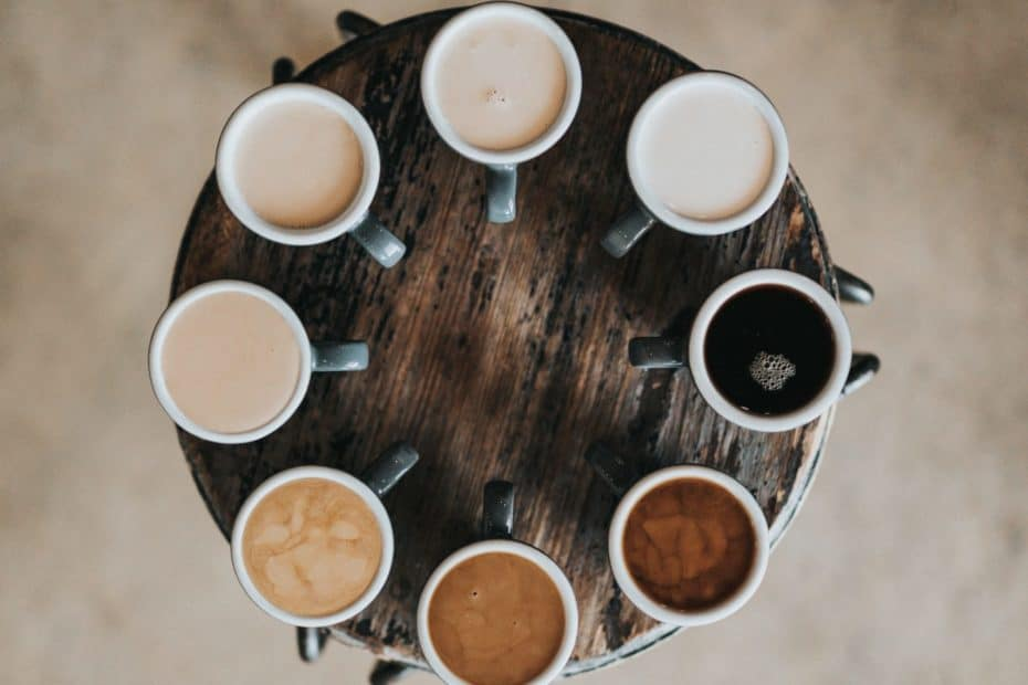 flat lay photography of eight coffee latte in mugs on round table